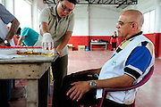 Cuban Dr. Raul Herrera Vald&eacute;z, scrutinising the work of a health practioner analysing the results of urine samples from members of the community of Ciudad Romero, as part of a series of medical investigations carried out by the 'Nefrolempa' health team into the high incidence of chronic renal failure in the region.<br /> <br /> Ciudad Romero, Bajo Lempa, El Salvador. 2011.<br /> The 'Nefrolempa' research project is a collaboration between the El Salvador Ministry of Health, the Nephrology Institute of Cuba's Ministry for Public Health and the United Bajo Lempa Committee Association. The aim of the project is to investigate the reasons for the high levels of Chronic Kidney Disease (CKD) suffered by the communities within the Bajo Lempa region. It is exploring whether the use of agrochemicals might be a factor in the prevalence of the disease.<br /> <br /> Medical team: Dr Elsy Brizuela de Jimenez, Directora Unidad de Salud. Miriam Colindres, Nurse. Maria Eraida Velasquez, clinic and laboratory worker. Ecuilia Castro Peraza, Nutritionist. Veronica Contreras, Education for health. Guadelupe Nunez, Psychologist. Luis Diaz General support worker. Dr Raul Herrera Valdes, Nefrologo, Cuba. Dr Miguel Almaguer Lopez, Nefrologo Cuba. Dr Carlos Orantes, Salvadorean Nefrologist. Dr Juan Carlos Awaya, Salvadorean Nefrologist.