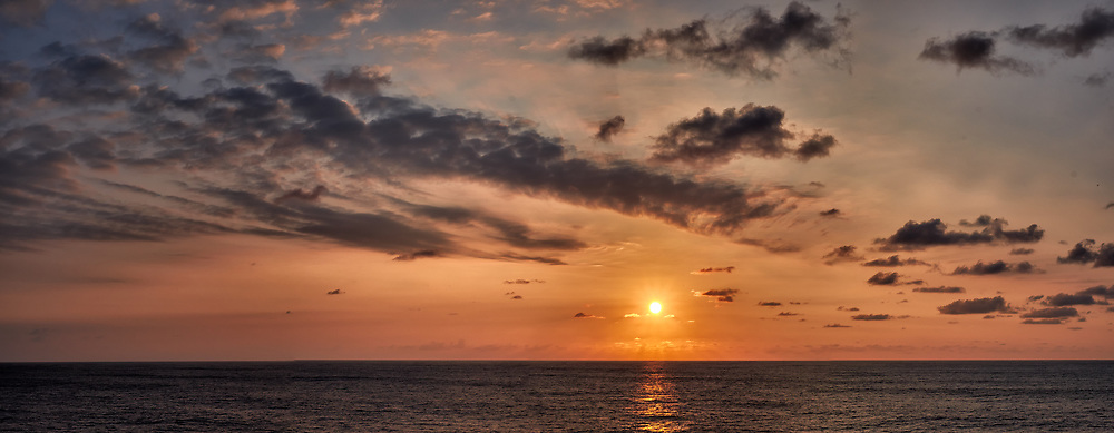 Orange colored sky and clouds over the Pacific Ocean just after sunrise. Composite of 10 images taken with a Fuji X-T1 camera and 35 mm f/1.4 lens  (ISO 200, 35 mm, f/16, 1/250 sec). Raw images processed with Capture One Pro and stitched together with AutoPano Giga Pro.