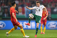 Andy King, right, of Wales national football team kicks the ball to make a pass against a player of Chinese national men's football team in the semi-final match during the 2018 Gree China Cup International Football Championship in Nanning city, south China's Guangxi Zhuang Autonomous Region, 22 March 2018.