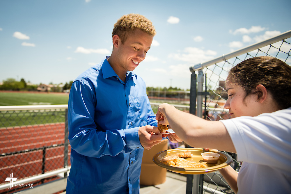 Chaz Read offers food condiments to Bailey Lamonte, a student in the Mark 10:14 Program, at an outdoor activity at Faith Lutheran Middle School & High School on Tuesday, May 26, 2015, in Las Vegas, Nev.  LCMS Communications/Erik M. Lunsford