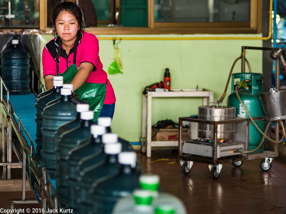 16 MARCH 2016 - BAN SONG, PRACHIN BURI, THAILAND: A worker pushes bottles of water down the line at a water bottling plant in Ban Song. The plant has been open for 11 years and is reporting that demand has increased above normal this year because more people are buying bottled water because salt water has intruded into the local water supply. Some people are buying the bottled water to wash and bathe with because of the salt water intrusion. The drought in Thailand is worsening and has spread to 14 provinces in the agricultural heartland of Thailand. Communities along the Bang Pakong River, which flows into the Gulf of Siam, have been especially hard hit since salt water has intruded into domestic water supplies as far upstream as Prachin Buri, about 100 miles from the mouth of the river at the Gulf of Siam. Water is being trucked to hospitals in the area because they can't use the salty water.    PHOTO BY JACK KURTZ