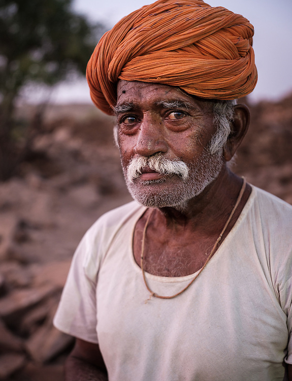 "JAISALMER, INDIA - CIRCA NOVEMBER 2018: Portrait of shepherd outside the ruins of Khabha Fort in Jaisalmer. Jaisalmer is also called ""The Golden City, and it is located in Rajasthan.  The town stands on a ridge of yellowish sandstone, and is crowned by the ancient Jaisalmer Fort."