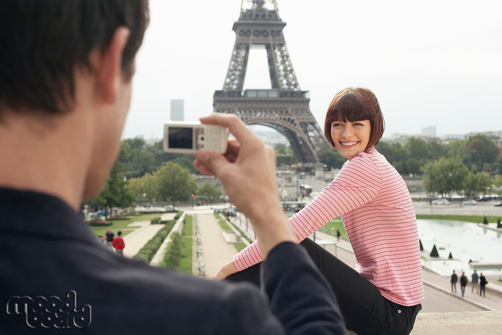 Couple Using Camera Phone and Eiffel Tower