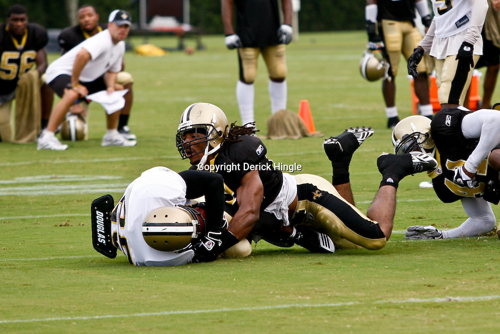 August 3, 2010; Metairie, LA, USA; New Orleans Saints safety Usama Young (28) hits running back Reggie Bush (25) on a run during a training camp practice at the New Orleans Saints practice facility. Mandatory Credit: Derick E. Hingle
