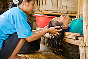 18 FEBRUARY 2008 -- BONG TI, KANCHANABURI, THAILAND: Burmese refugee women wash their hair at the Bamboo School in Bong Ti, Thailand, about 40 miles from the provincial capital of Kanchanaburi. Sixty three children, most members of the Karen hilltribe, a persecuted ethnic minority in Burma, live at the school under the care of Catherine Riley-Bryan, whom the locals call MomoCat (Momo is the Karen hilltribe word for mother). She provides housing, food and medical care for the kids and helps them get enrolled in nearby Thai public schools. Her compound is about a half mile from the Thai-Burma border. She also helps nearby Karen refugee villages by digging water wells for them and providing medical care.  Photo by Jack Kurtz