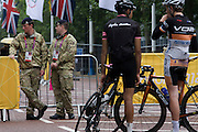 Cyclists with soldiers the Royal Artillery regiment in the British army stand guarding the entrance to  the volleyball venue in central London next to the IOC rings logo on day 4 of the London 2012 Olympic Games.  A total of 18,000 defence personel were called upon to make the Games secure following the failure by security contractor G4S to provide enough private guards. The extra personnel have been drafted in amid continuing fears that the private security contractor's handling of the £284m contract remains a risk to the Games.