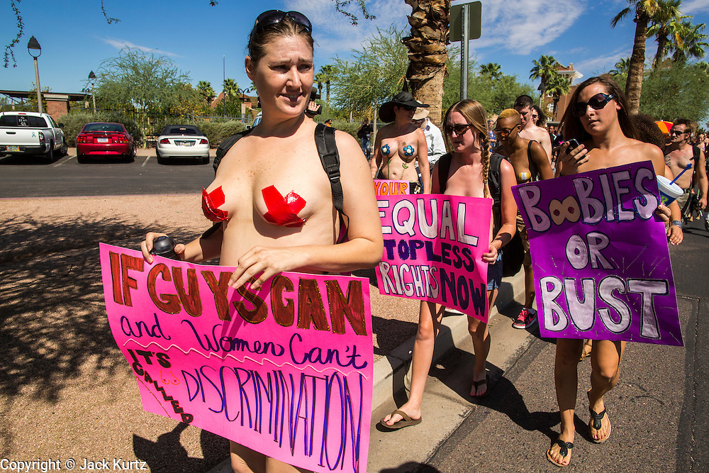 26 MARCH 2012 - PHOENIX, AZ:  KELLY CAYE, a topless protester, at a topless protest in Phoenix. About 40 people marched through central Phoenix Sunday to call for a constitutional amendment to give women the same right to go shirtless in public that men have. The Phoenix demonstration was a part of a national Topless Day of Protest. Phoenix prohibits women from going topless in public so protesters, women and men, covered their nipples and areolas with tape. The men did it to show solidarity with the women marchers.   PHOTO BY JACK KURTZ