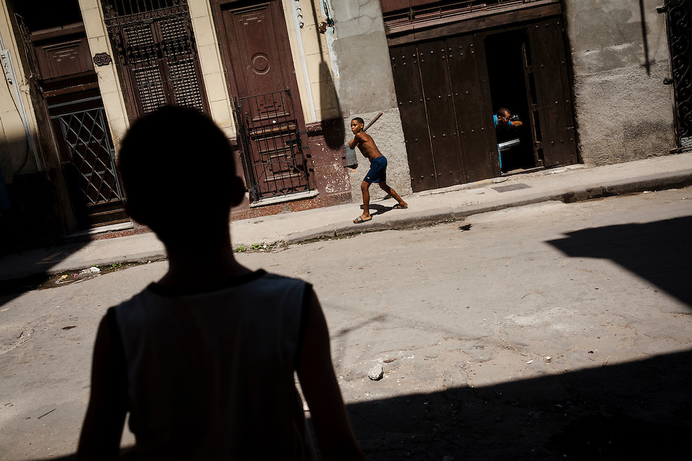 Kids practice their baseball skills with a stick and bottle top in Havana, Cuba