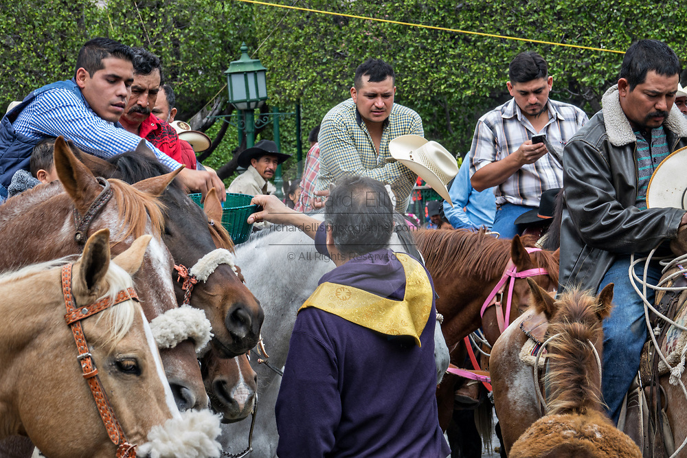 Mexican cowboys donate money following Catholic Mass in the Jardin Allende at the end of their pilgrimage celebrating the festival of Saint Michael in San Miguel de Allende, Mexico.