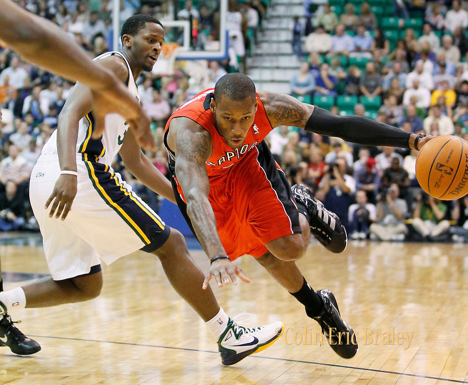 Toronto Raptors guard Sonny Weems, right, is tripped up by Utah Jazz forward C.J. Miles, left, during the first half of NBA play in Salt Lake City, Wednesday, November 3, 2010. (AP Photo/Colin E Braley)