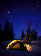 Idaho, winter camping. Glowing tent with star trails.