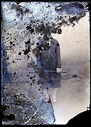 severely eroding glass plate of adult woman standing and holding an umbrella