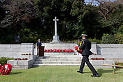 A man in military uniform lays a wreath of poppies at The Cross of Sacrifice during the Remembrance Sunday ceremony at the Hodogaya, Commonwealth War Graves Cemetery in Hodogaya, Yokohama, Kanagawa, Japan. Sunday November 11th 2018. The Hodagaya Cemetery holds the remains of more than 1500 servicemen and women, from the Commonwealth but also from Holland and the United States, who died as prisoners of war or during the Allied occupation of Japan. Each year officials from the British and Commonwealth embassies, the British Legion and the British Chamber of Commerce honour the dead at a ceremony in this beautiful cemetery. The year 2018 marks the centenary of the end of the First World War in 1918.