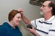 With Victoria Theatre Association public-relations manager Diane Schoeffler-Warren as a model, Patrick Keough holds the wireless transmitter as he shows the first steps of how the body mics they use  can be placed (and then hidden) on some performers at the Schuster Center in downtown Dayton, Friday, January 27, 2012.  Keough says other times they attach a mic to clothing or use a piece that goes over the ear.