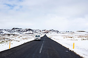 Car motoring on main tarmac road route  from Reykjavik though lava fields in South Iceland with snow depth markers on the roadside.