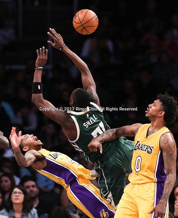 3月17日,密尔沃基雄鹿队球员托尼-斯内尔 (中)在比賽中上篮被洛杉矶湖人队球员侵犯。 当日,在2016-2017赛季NBA常规赛中,洛杉矶湖人队主场以103比107不敌密尔沃基雄鹿队。 新华社发 (赵汉荣摄)<br /> Milwaukee Bucks guard Tony Snell (#21) gets fouled by Los Angeles Lakers forward Thomas Robinson (#15) during an NBA basketball game, Friday, March 17, 2017.(Photo by Ringo Chiu/PHOTOFORMULA.com)<br /> <br /> Usage Notes: This content is intended for editorial use only. For other uses, additional clearances may be required.