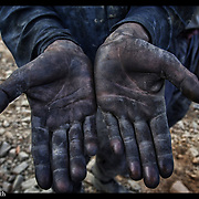 The soiled hands of an Afghanistan brickmaker are seen near Kabul, Afghanistan, 27 Aug. 2002.