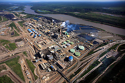CANADA ALBERTA FORT MCMURRAY 20JUL09 - Aerial view of Suncor upgrader plant next to the Athabasca river in the Boreal forest north of Fort McMurray, northern Alberta, Canada...The tar sand deposits lie under 141,000 square kilometres of sparsely populated boreal forest and muskeg and contain about 1.7 trillion barrels of bitumen in-place, comparable in magnitude to the world's total proven reserves of conventional petroleum. Current projections state that production will  grow from 1.2 million barrels per day (190,000 m³/d) in 2008 to 3.3 million barrels per day (520,000 m³/d) in 2020 which would place Canada among the four or five largest oil-producing countries in the world...The industry has brought wealth and an economic boom to the region but also created an environmental disaster downstream from the Athabasca river, polluting the lakes where water and fish are contaminated. The native Indian tribes of the Mikisew, Cree, Dene and other smaller First Nations are seeing their natural habitat destroyed and are largely powerless to stop or slow down the rapid expansion of the oil sands development, Canada's number one economic driver...jre/Photo by Jiri Rezac / GREENPEACE..© Jiri Rezac 2009
