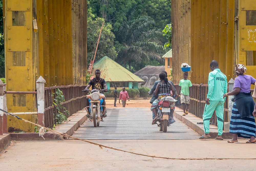 Various people travel across bridge on foot and on motorcycles in Republic of Guinea