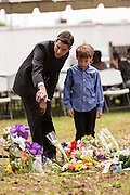 The Rev. Jeremy Rutledge and his son view a makeshift memorial on the spot where unarmed motorist Walter Scott was gunned down by police April 12, 2015 in North Charleston, South Carolina. About 100 people showed up for the brief vigil following a healing service at Charity Mission Baptist Church.