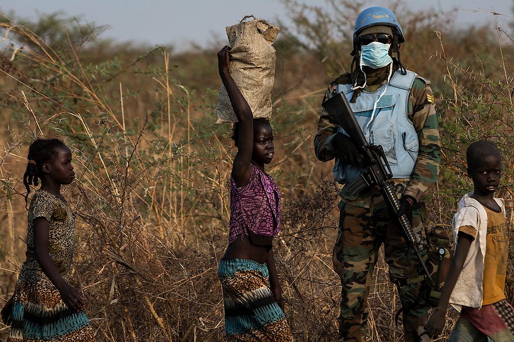 A United Nations Mission in South Sudan (UNMISS)  peacekeeping soldier stands guard as children walk by during a foot patrol close to the town of Bentiu in Rubkona county, South Sudan.
