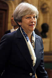 Prime Minister Theresa May walks through the Palace of Westminster to the House of Lords after attending the State Opening of Parliament in London