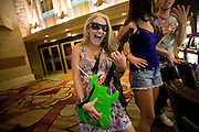 A woman celebrates a birthday with a plastic guitar, which doubles as a cocktail container, in Las Vegas, Nevada.