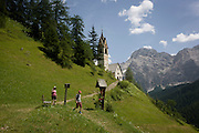 Walkers downhill from the church of Santa Berbura, founded and built by iron miners in 1490, in the Dolomites near La Val in Alta Badia, south Tyrol, Italy.