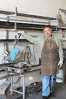 Portrait of a mature man standing by electric saw in workshop