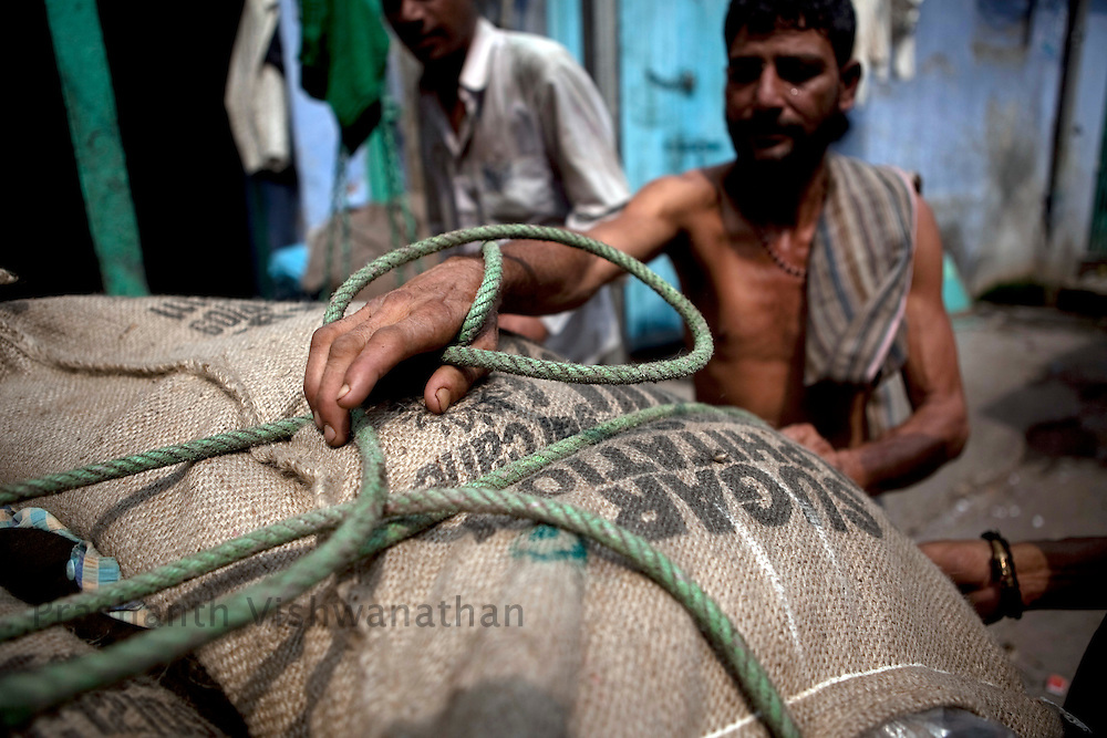 Labourers arrange 50 kg bags of sugar, on a hand cart to be transported to vendors, at the wholesale market of Old Delhi, in New Delhi, India, on Wednesday September 2, 2010. Photographer: Prashanth Vishwanathan/Bloomberg News