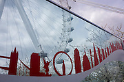London landmarks designed into a glass panel with the circular London Eye ferris wheel and a cloudy sky.