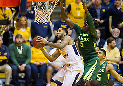 Jan 10, 2017; Morgantown, WV, USA; West Virginia Mountaineers guard Tarik Phillip (12) shoots under the basket while defended by Baylor Bears forward Johnathan Motley (5) during the first half at WVU Coliseum. Mandatory Credit: Ben Queen-USA TODAY Sports
