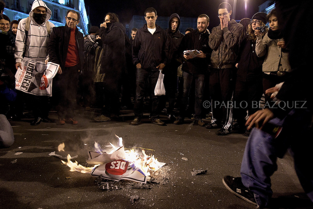 Protesters burn politics propaganda from the main parties during 'indignant' demonstration in Puerta del Sol square in Madrid on November 19, 2011 against spending cuts, high unemployment and political corruption, one day before general election. Spain's so-called 'indignant' protest movement was born when thousands of people set up camp in Madrid's Puerta del Sol square ahead of May 22 municipal elections.