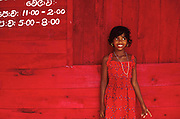 Girl in red dress on west coast standing in front of the red painted panels of a toddy tavern.