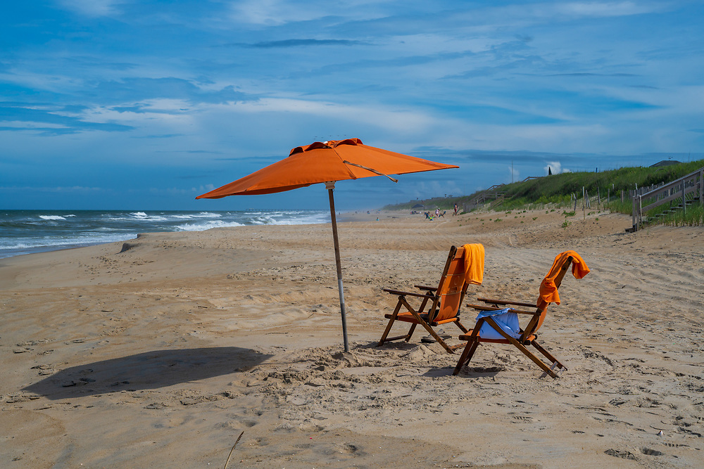 Two orange beach chairs and a matching umbrella are set up facing the ocean in the Outer Banks of North Carolina.