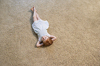 Young girl (5-6) lying on carpet view from above