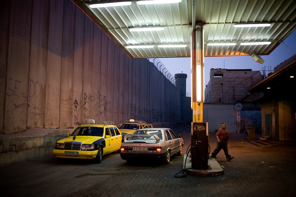 A Palestinian owned petrol station in the shadow of the Israeli security wall in Bethlehem. 14th May 2008