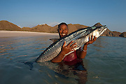 Fisherman with Narrow-barred or Spanish Mackerel (Scomberomorus commerson) in Komodo National Park, Indonesia.