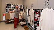 Equipment managers work in the Mal Moore Athletic Facility to get the University of Alabama football team ready for the trip to Baton Rouge to face LSU.  Student equipment manager Kyle Smith tosses a box of socks to another manager as they pack for the trip.  Photo by Gary Cosby Jr.