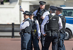 © Licensed to London News Pictures. 24/05/2017. London, UK. Police gather outside Buckingham Palace - security in the capital has been stepped up after the Manchester Arena bombing. The terrorism threat level has been raised to critical and Operation Temperer has been deployed. 5,000 troops are taking over patrol duties under police command. Photo credit: Peter Macdiarmid/LNP