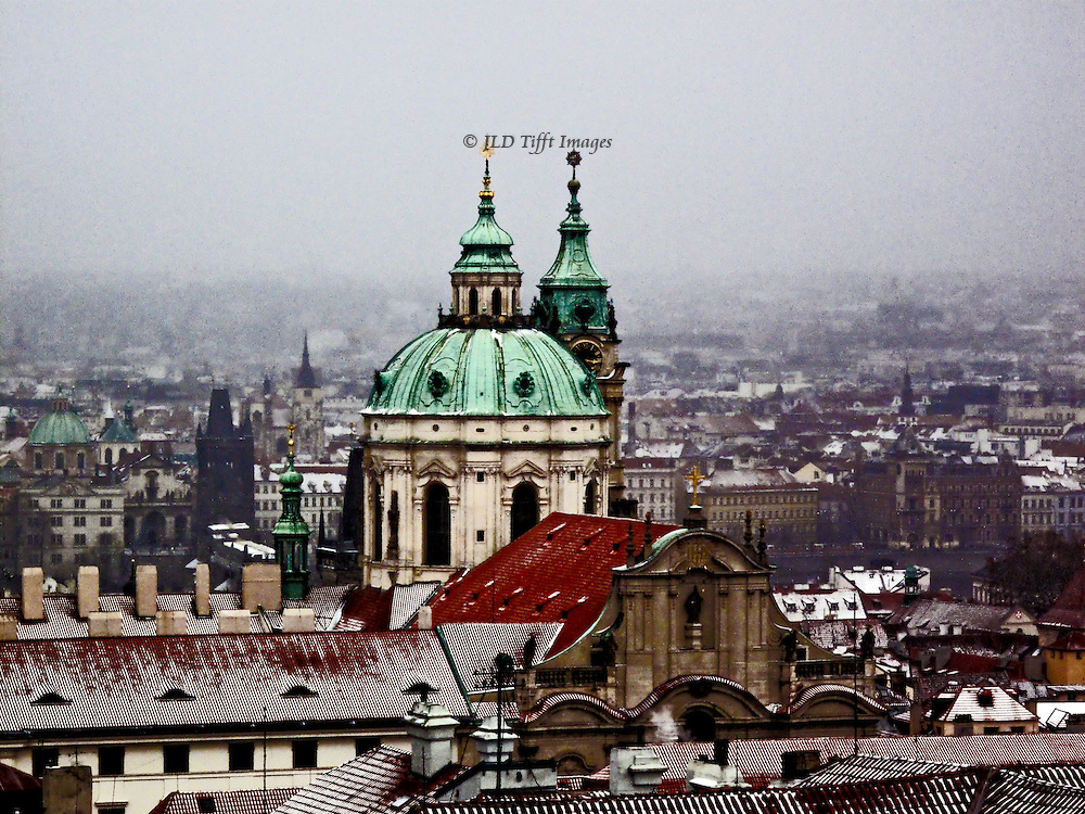 Prague rooftops under snow, seen from Hradcany above. Dome and spire of St. Nicholas church in the Lesser Town Square dominate the scene.