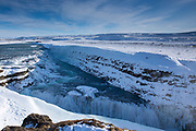 Gushing, flowing glacial river water at falls of Gullfoss Waterfall and mountains in glacial landscape of South Iceland