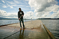 Zac Loy pressure washes a dock Tuesday at The Coeur d'Alene Resort Golf Course under cloudy skies. The break in the wet weather only lasted the day as more rain is forecasted through the week.