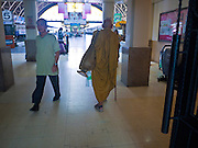 11 JULY 2011 - BANGKOK, THAILAND:   A Buddhist monk walks out to the platforms in Hua Lamphong station in Bangkok. Hua Lamphong Grand Central Railway Station, officially known as the Bangkok Grand Central Terminal Railway Station, is the main railway station in Bangkok, Thailand. It is located in the center of the city in Pathum Wan District, and is operated by the State Railway of Thailand. The station was opened on 25 June 1916, after six years' construction. The station was built in an Italian Neo-Renaissance style, with decorated wooden roofs and stained glass windows. The architecture is attributed to Turin-born Mario Tamagno, who, with countryman Annibale Rigotti made a mark on early 20th century public building in Bangkok. The pair also designed Bang Khun Prom Palace (1906), Ananda Samakhom Throne Hall in The Royal Plaza (1907-15) and Suan Kularb Residential Hall and Throne Hall in Dusit Garden, among other buildings..There are 14 platforms and 26 ticket booths. Hua Lamphong serves over 130 trains and approximately 60,000 passengers each day. Thailand has the most advanced rail system in Southeast Asia and trains from Hua Lamphong serve all corners of the Kingdom.       PHOTO BY JACK KURTZ