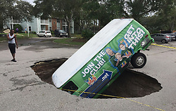"Residents of the Astor Park apartment complex off Tuskawilla Road in Winter Springs, FL, USA were shocked to find a van head first in a sinkhole in the parking lot. The driver apparently crawled out by kicking out the back window of the vehicle. ""It's very strange and very scary,"" resident Mario Lopez said. Photo by Joe Burbank/Orlando Sentinel/TNS/ABACAPRESS.COM"