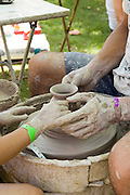 Potter teaching a young child to make a clay pot while guiding her hands on the clay