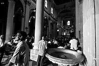 Lecce - Processione precedente la Santa Messa in onore del Santo. Fedele davanti all'acquasantiera attende l'inizio della Santa Messa il giorno 26 agosto.