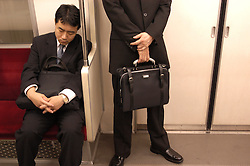 Two male commuters travelling on the Tokyo Subway train