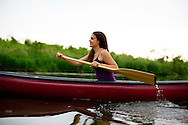 Woman rowing a canoe in a river.