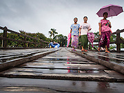 17 SEPTEMBER 2014 - SANGKHLA BURI, KANCHANABURI, THAILAND: Members of the Mon community walk along a repaired section of the Mon Bridge. The 2800 foot long (850 meters) Saphan Mon (Mon Bridge) spans the Song Kalia River. It is reportedly second longest wooden bridge in the world. The bridge was severely damaged during heavy rainfall in July 2013 when its 230 foot middle section  (70 meters) collapsed during flooding. Officially known as Uttamanusorn Bridge, the bridge has been used by people in Sangkhla Buri (also known as Sangkhlaburi) for 20 years. The bridge was was conceived by Luang Pho Uttama, the late abbot of of Wat Wang Wiwekaram, and was built by hand by Mon refugees from Myanmar (then Burma). The wooden bridge is one of the leading tourist attractions in Kanchanaburi province. The loss of the bridge has hurt the economy of the Mon community opposite Sangkhla Buri. The repair has taken far longer than expected. Thai Prime Minister General Prayuth Chan-ocha ordered an engineer unit of the Royal Thai Army to help the local Mon population repair the bridge. Local people said they hope the bridge is repaired by the end November, which is when the tourist season starts.    PHOTO BY JACK KURTZ